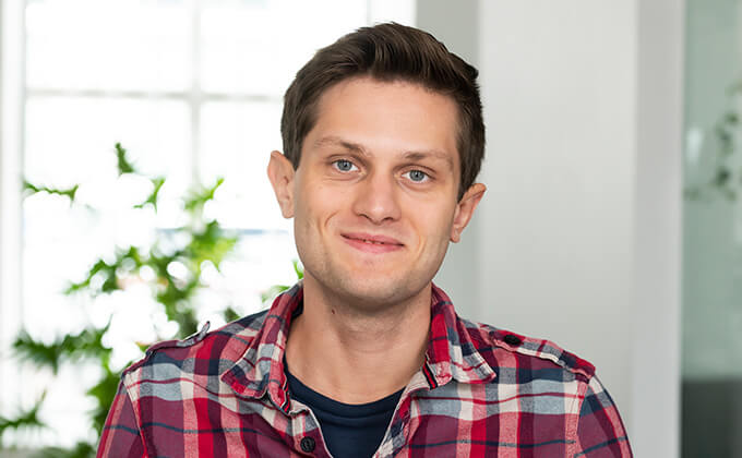 Image for En ung man med rödrutig skjorta, blå ögon och mörkt hår som ler mot kameran.