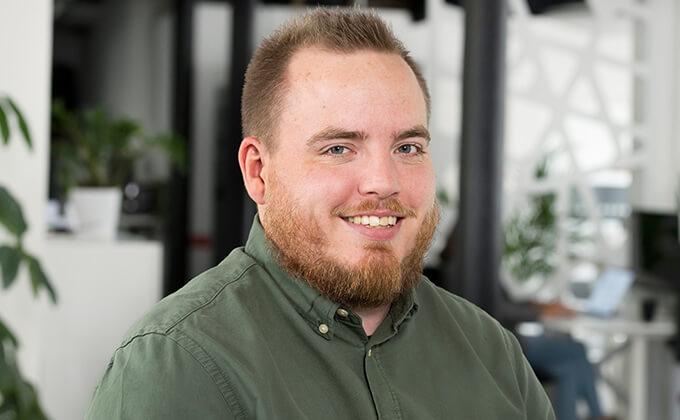 Image for En man med grön skjorta och skägg som ler mot kameran.