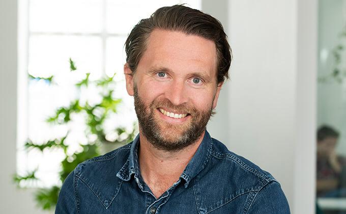 Image for En man med kortskägg, blå skjorta och brunt hår som ler in i kameran.