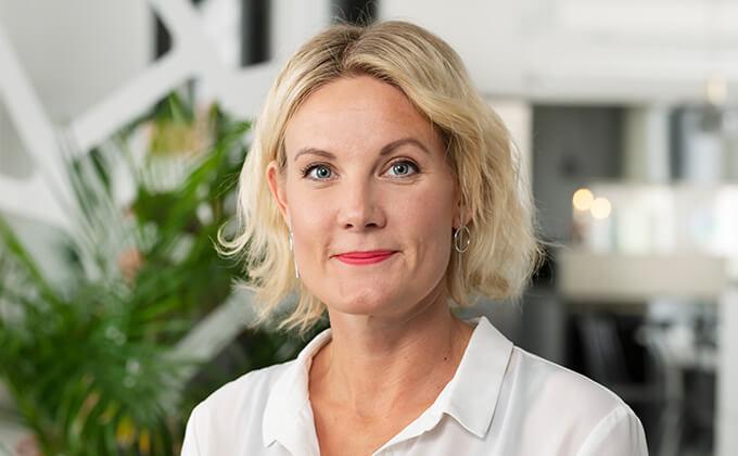 Image for En leende kvinna med blont halvkort hår, rött läppstift och vit skjorta.