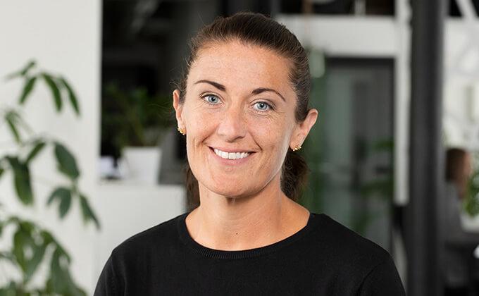 Image for En kvinna med mörkt hår och blåa ögon som ler in i kameran.