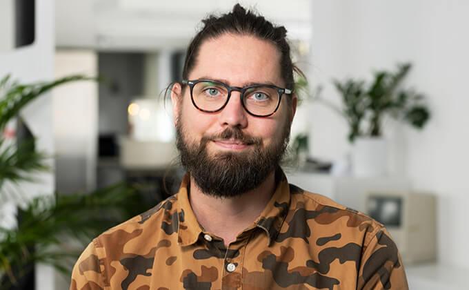 Image for En man med glasögon och skägg som tittar in i kameran.