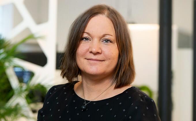 Image for Kvinna med mörkt hår i en page frisyr som leer mot kameran