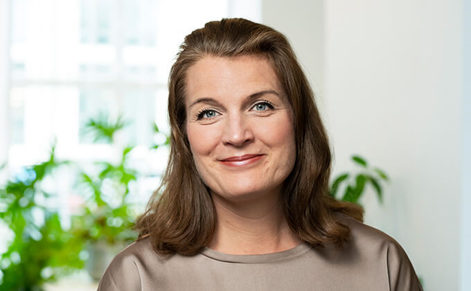 Image for En kvinna men mörkt hår, blå ögon och rött läppstift. Bakom henne ser man en grön växt i ett fönster.